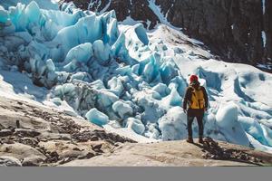 homme voyageur debout sur un rocher sur le fond d'une glacie photo