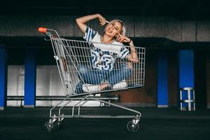 femme vêtue de jeans avec des caddies dans le parking photo