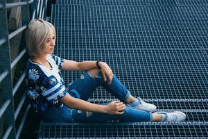 femme aux cheveux blancs courts dans un style urbain est assise sur les escaliers métalliques photo