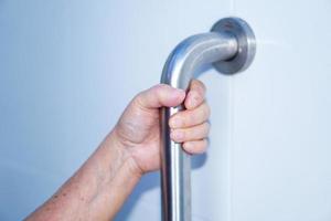 femme senior asiatique patient utiliser toilettes salle de bain poignée sécurité photo