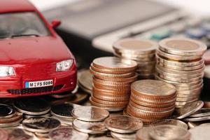 voiture sur des pièces de monnaie. prêt automobile, finance, économiser de l'argent, assurance, crédit-bail photo