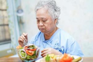 patiente asiatique âgée prenant son petit déjeuner à l'hôpital. photo