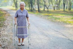 femme âgée asiatique utilise un marcheur dans le parc. photo
