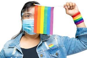 dame asiatique tenant un drapeau de couleur arc-en-ciel, symbole de lgbt photo