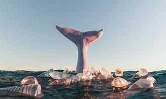 queue de baleine dans l'océan entourée de bouteilles en plastique photo