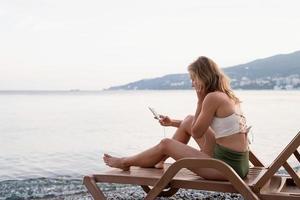 jeune femme assise sur la chaise longue écoutant de la musique photo