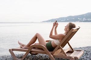 jeune femme allongée sur la chaise longue écoutant de la musique photo