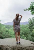 Jeune femme debout sur un gros rocher dans la forêt à l'écart photo
