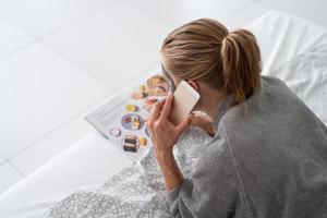 femme avec masque facial relaxant allongé sur le lit en lisant un magazine photo