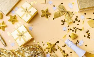 vue de dessus des décorations de fête dorées avec des confettis et des coffrets cadeaux photo