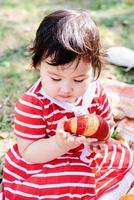 mignon petit bébé dans une robe rouge et un chapeau srtaw sur un pique-nique dans le parc photo