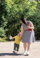 heureuse famille multiraciale de mère et fille marchant dans le parc photo