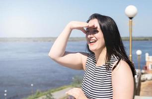 Jeune femme riante debout au bord de la rivière en profitant de la vue photo