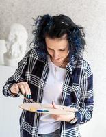 femme créative avec la peinture de cheveux teints en bleu dans son studio photo