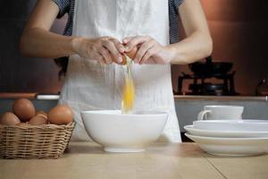 une cuisinière dans un tablier blanc casse un œuf dans la cuisine de la maison. photo