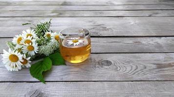 thé à la camomille et bouquet de camomille photo