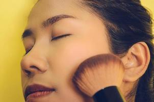 visage de beauté d'une femme asiatique en appliquant des pinceaux sur la peau par des cosmétiques. photo