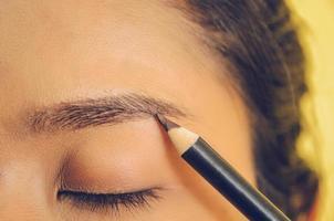 visage de beauté d'une femme asiatique en appliquant un crayon à sourcils sur la peau. photo