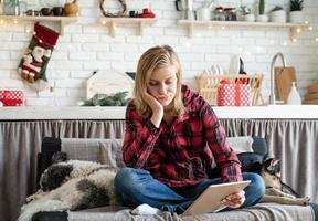 jeune femme triste en travaillant sur tablette assis sur le canapé photo