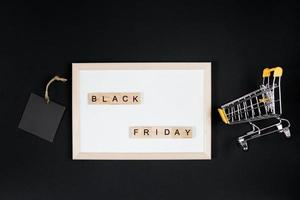 vente du vendredi noir. mini panier dans le cadre sur fond noir. photo