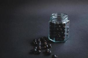 bocal en verre avec des baies de groseille sur fond noir. photo