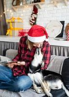 Woman in santa hat working on tablet assis sur le canapé avec son chien photo