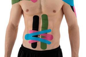 bodybuilder avec bandes élastiques de kinésiologie sur l'abdomen abdominal. photo
