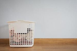 panier à linge en plastique sur plancher en bois photo