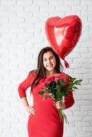 femme tenant un ballon coeur rouge et des fleurs photo