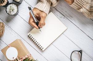 une main tenant un stylo pour écrire sur un cahier avec des lunettes photo