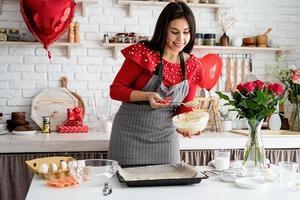 femme faisant des biscuits de la Saint-Valentin à la cuisine photo