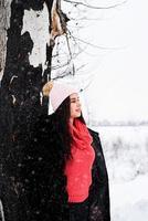 Portrait d'une jeune femme souriante debout près de l'arbre dans les chutes de neige photo