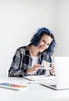 designer travaillant avec des palettes de couleurs et un ordinateur portable dans son studio photo