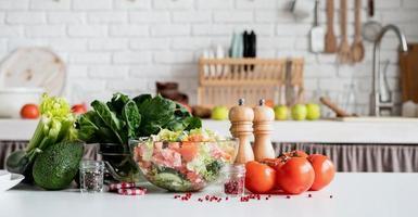 vue de face de la table de cuisine avec un bol de salade grecque et d'ingrédients photo