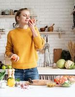 Vue de face d'une jeune femme sentant la tomate, faisant de la salade dans la cuisine photo