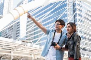 touriste de couple asiatique regardant et pointant le doigt vers l'avant photo