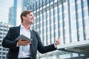 jeune homme d'affaires se sentant heureux holding tablet photo