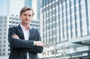 homme d'affaires debout avec les bras croisés sur fond de construction d'entreprise photo