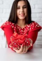 femme en robe rouge tenant un cadeau pour la saint valentin photo