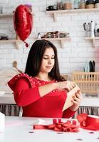 Femme écrivant une lettre d'amour assise à la cuisine décorée photo