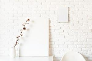 maquette de cadre d'affiche avec une branche de coton sur fond de mur de briques blanches photo