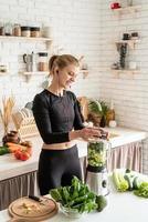 Jeune femme souriante blonde faisant un smoothie vert à la cuisine à la maison photo