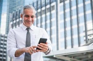 portrait d'un homme d'affaires senior utilisant un téléphone photo