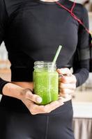 femme en tenue de sport noire tenant un pot de smoothie vert photo