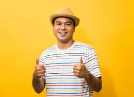jeune homme asiatique avec un chapeau se sent heureux et surpris en montrant le pouce vers le haut photo