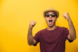 heureux jeune homme asiatique célèbre avec les deux mains en l'air photo