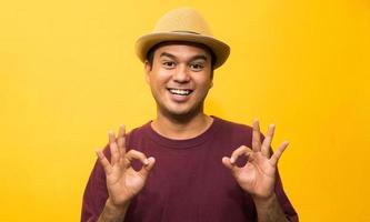 jeune homme asiatique montrant le signe ok de la main sur fond jaune. photo