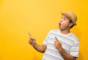 jeune homme asiatique drôle heureux pointant le doigt sur un espace vide photo