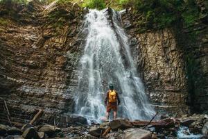 homme avec un sac à dos près d'une cascade photo
