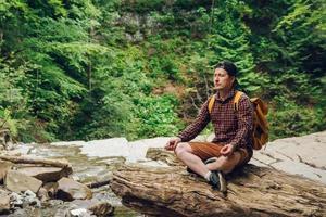 homme méditant en forêt avec une rivière photo